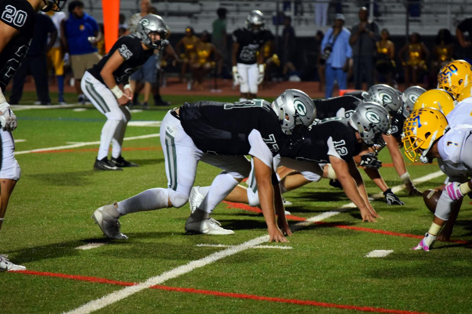 Varsity football team squares up on the line.