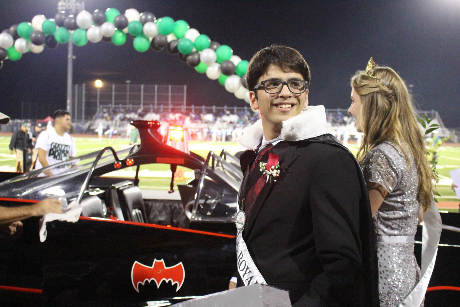 Senior King Rami Sadek and Queen Taylor Harris celebrate their victory with a ride in the Bat-Mobile.