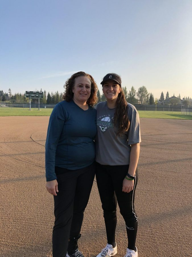 Lindsey+Poulos+poses+with+her+mother%2C+Michele+Granger+on+the+softball+field+after+softball+practice.