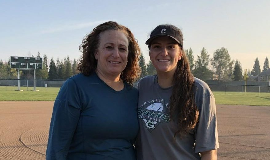 Lindsey Poulos poses with her mother, Michele Granger on the softball field after softball practice.