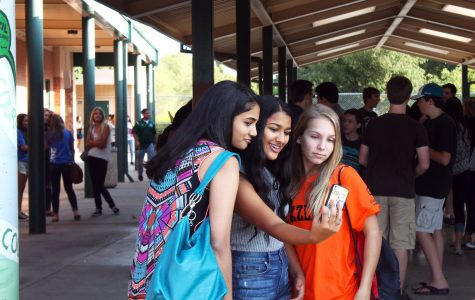 "#SELFIE Stopping to snap a quick selfie, freshmen Tanvi Yadlapalli, Anvita  Gattani, and Sienna Unter are all smiles as they enjoy a backpack-free first day of school. This year, school started with a special 20th anniversary celebration that included rallies, meetings, and best of all, no backpacks! ""I liked it because you didn't have to stress that much on the first day of school"", Yadlapalli said. ""But I still brought a handbag to put my lunch and phone in."" Photo by Frances Strnad"