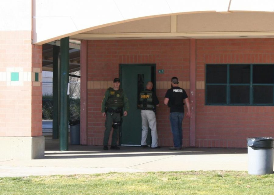 Law enforcement officers enter the GBHS front office during Tuesday's lockdown.