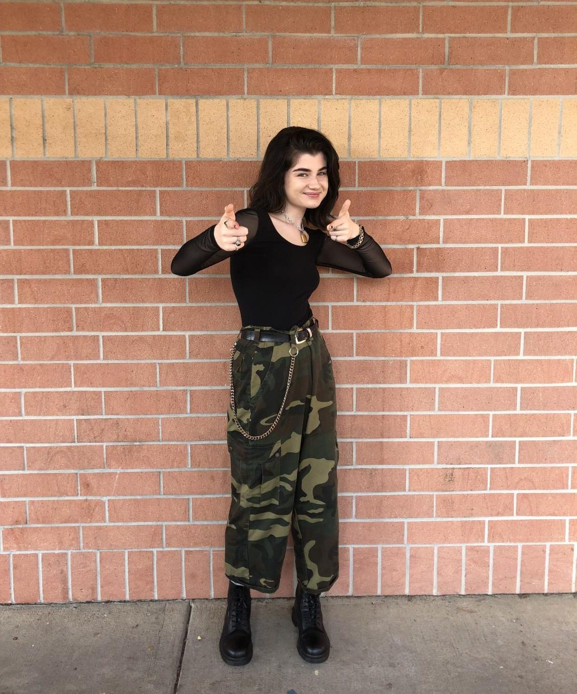 Kenzie Keith poses in an outfit with a green and black color scheme.