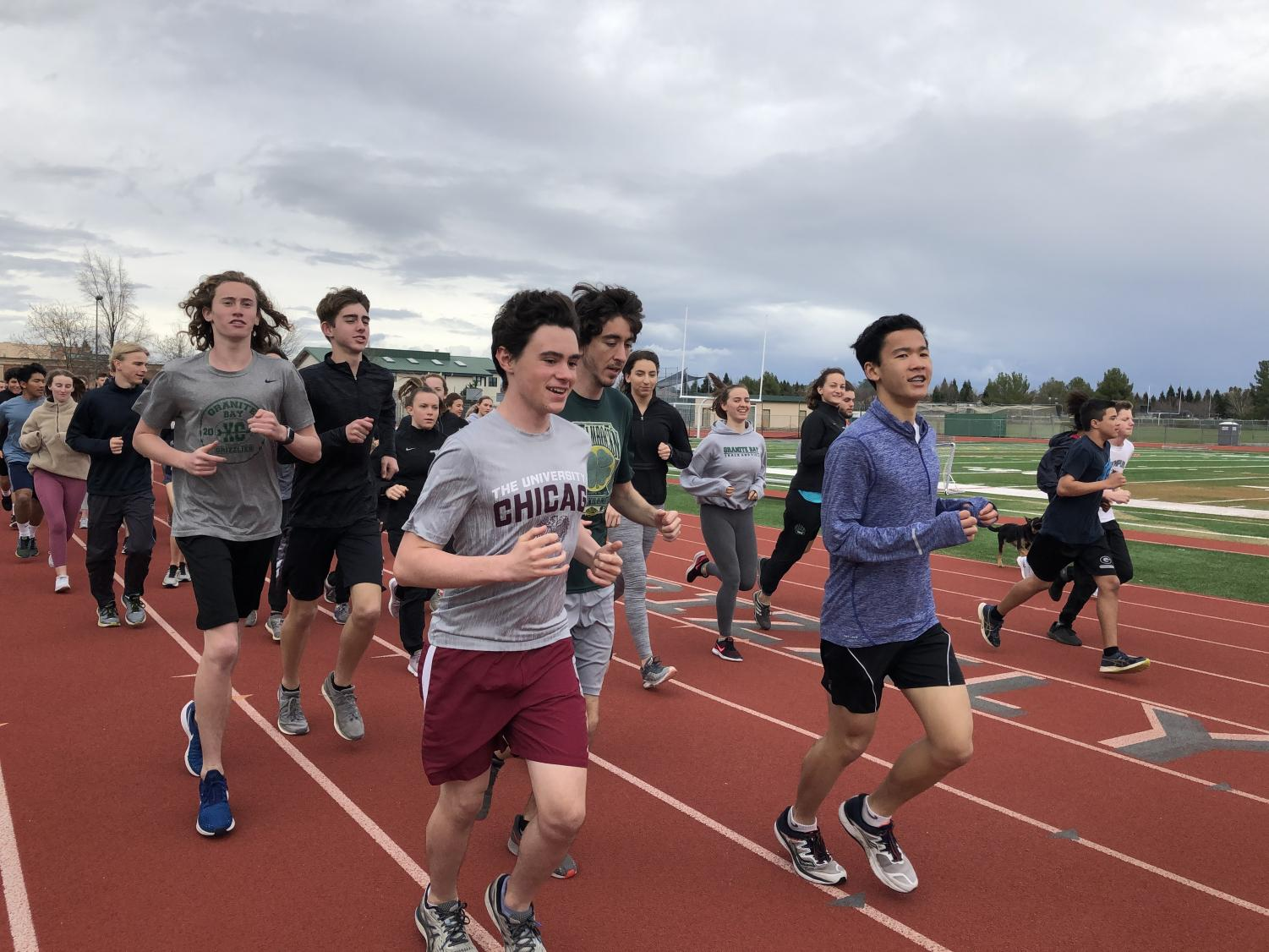The track and field team runs warm-up laps for an after-school practice session.