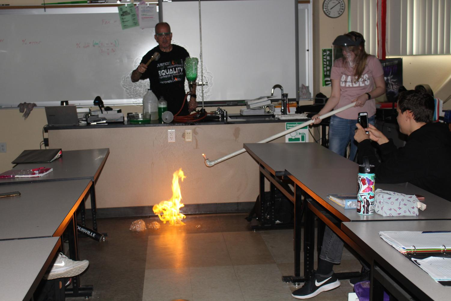 Junior Ivy Fralix launches a ball of flame during a lab in Stephen Miller's fourth period CP Physics class, students must be prepared for activities like this in NGSS Physics.