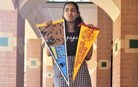GBHS graduate Manvi Bhapkar holds up two college banners and deliberates about the different college she was considering for her freshman year of college.