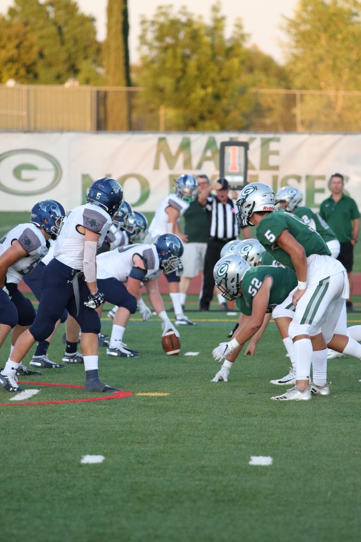 Varsity+football+team+begins+the+game.