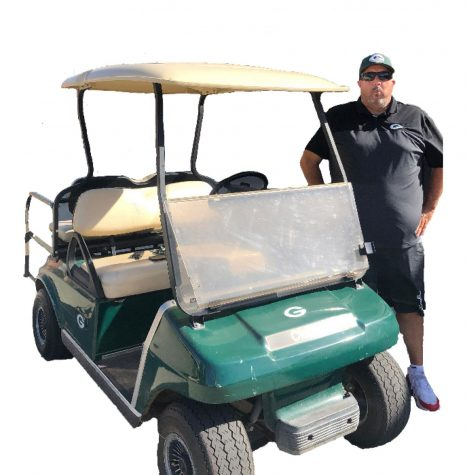 Campus monitor, Jason Ott, poses next to his infamous golf cart.