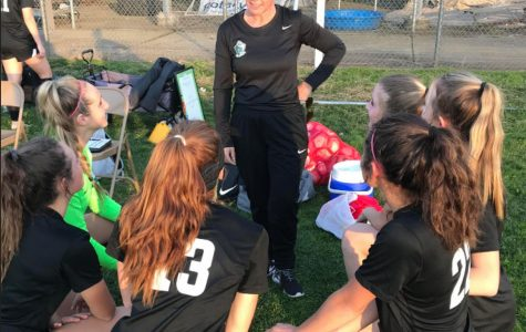 Varsity girls soccer players take a knee at one of their last games with their coach, Katy Vivaldi.