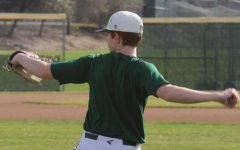 Varsity baseball player Derek Schwarze rounds up to practice his throw on the field.