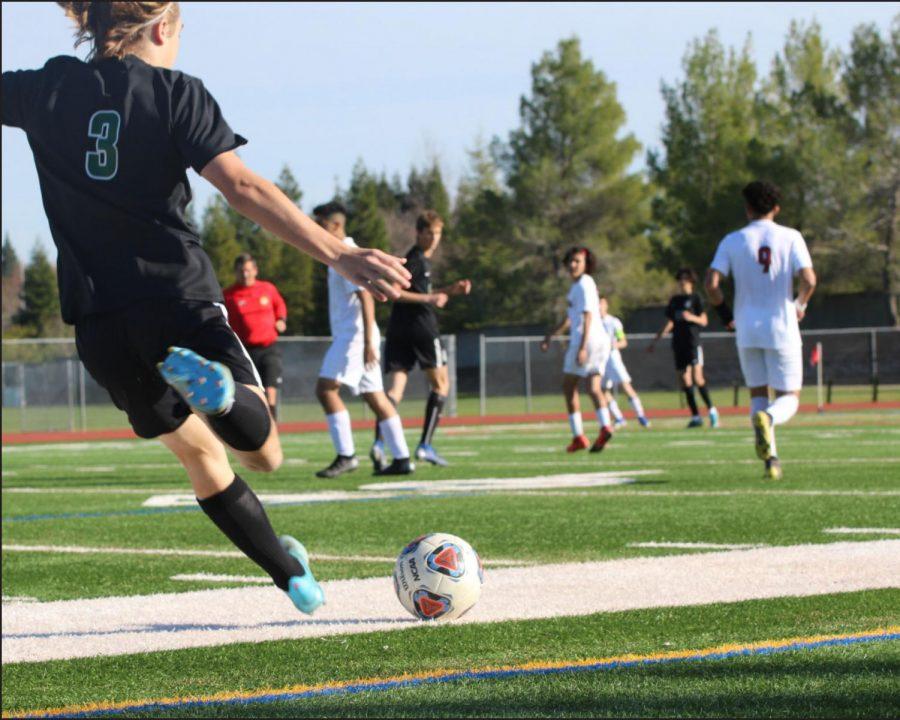 Varsity soccer player Luke Garman winds up to send the ball toward his teammates.