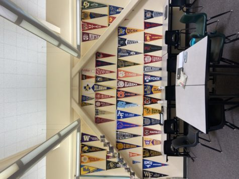 """Mr. Moore dedicates his back wall full to his former students. """"When they go off to [college] they get one of those [pennants] for the school they go to, Moore said.  Along with the pennants, some students will send in holiday cards or postcards, which he places frames on the left diagonal beam."""