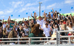 The crowd goes wild when the school mascot, Big G, makes his way through the bleachers to greet students during the homecoming spirit rally.